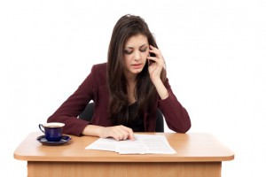 Young businesswoman speaking on phone while reading documents